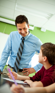 Male Teacher Assists Student in Classroom