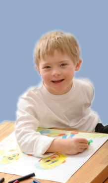 Young Boy With Down Syndrom Coloring at Desk