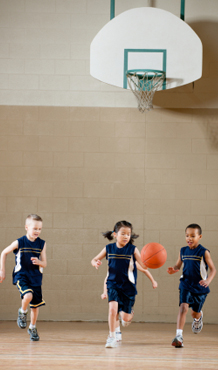 Three Young children playing basketball in school gym