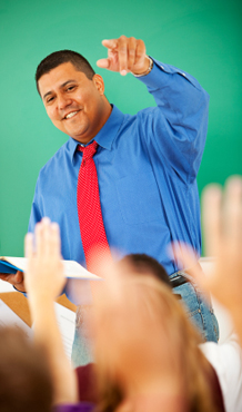Male teacher at front of class calling on the students with raised hands