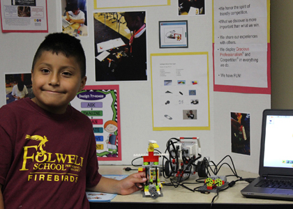 Kevin from the Minneapolis Community Education's Folwell Performing Arts Magnet afterschool program proudly shares his robotics project