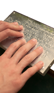 Hands reading braille plaque
